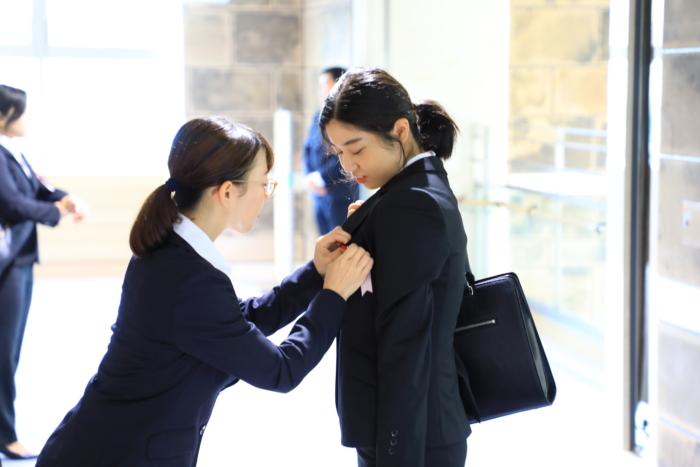 胸章をつけてもらう内定者と受け付けの女性