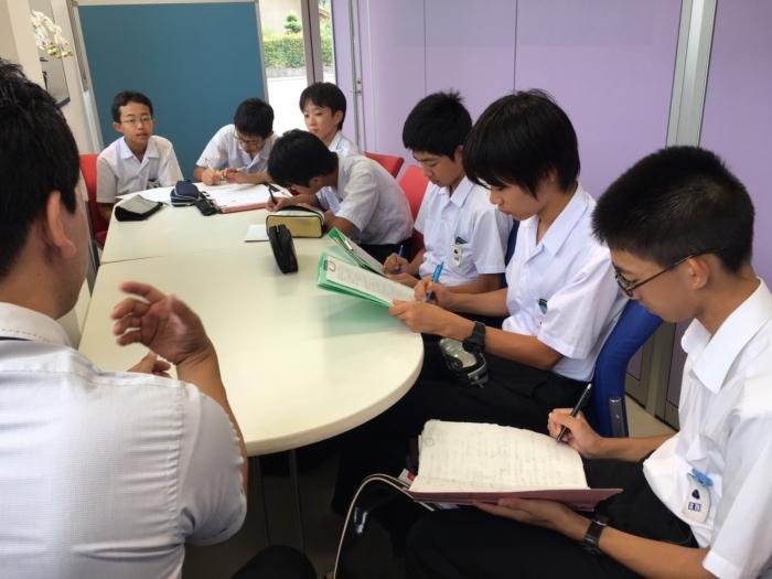 話をメモする男子学生7人と男性社員